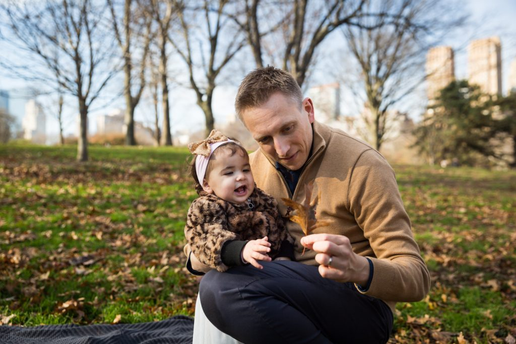 Father showing leaf to little girl in Central Park