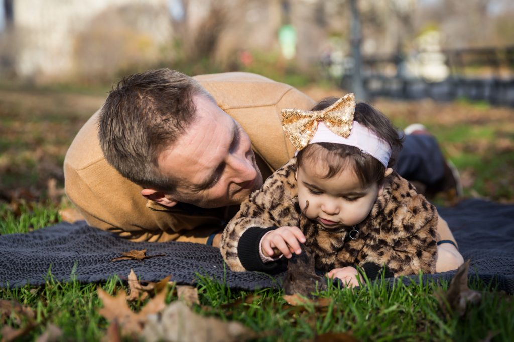 Father laying on blanket with little girl