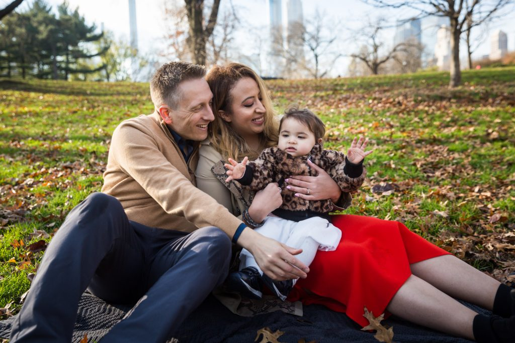 Parents sitting with little girl in the grass in Central Park