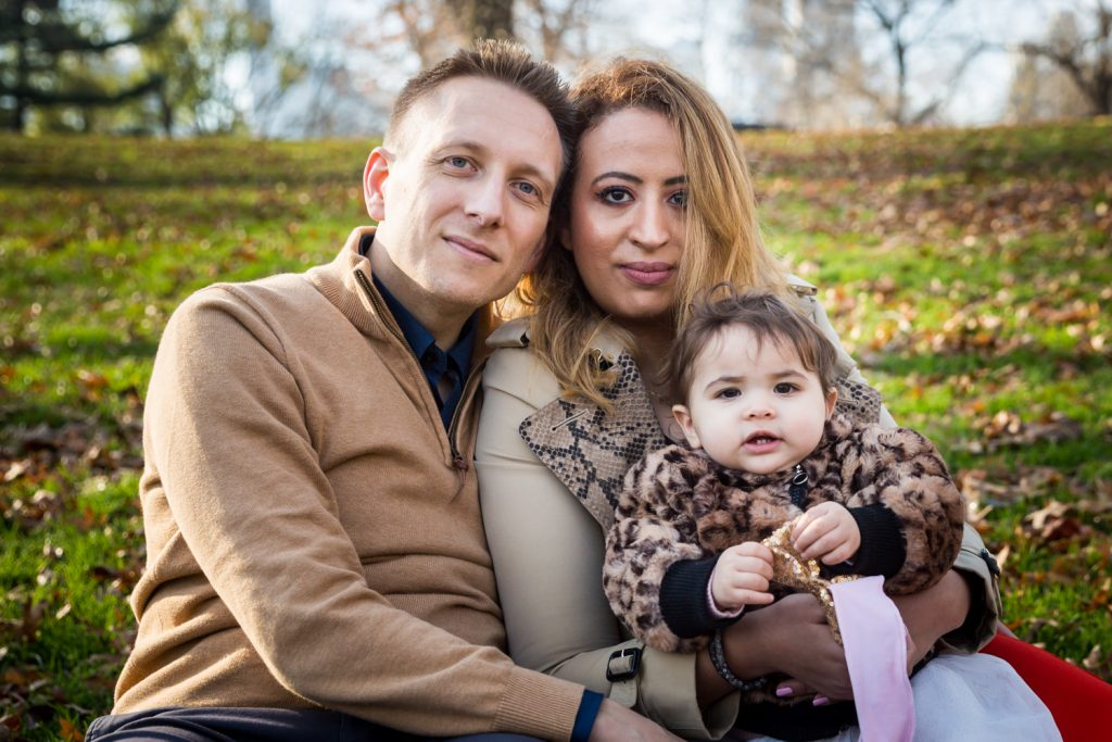 Parents holding little girl in the grass in Central Park