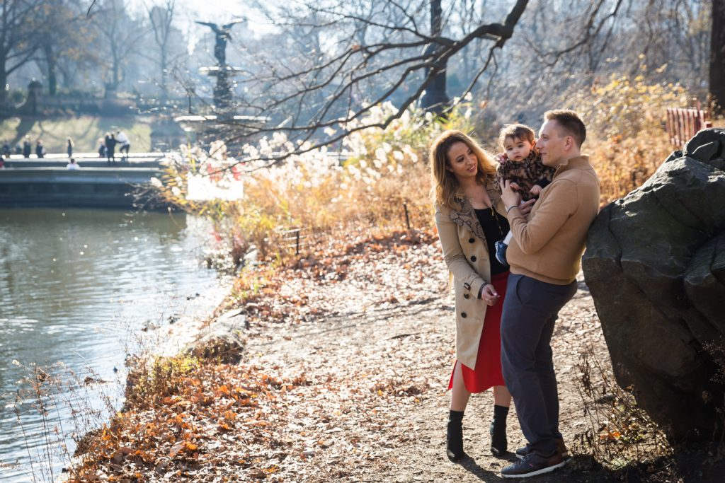 Parents and little girl standing by Central Park Lake