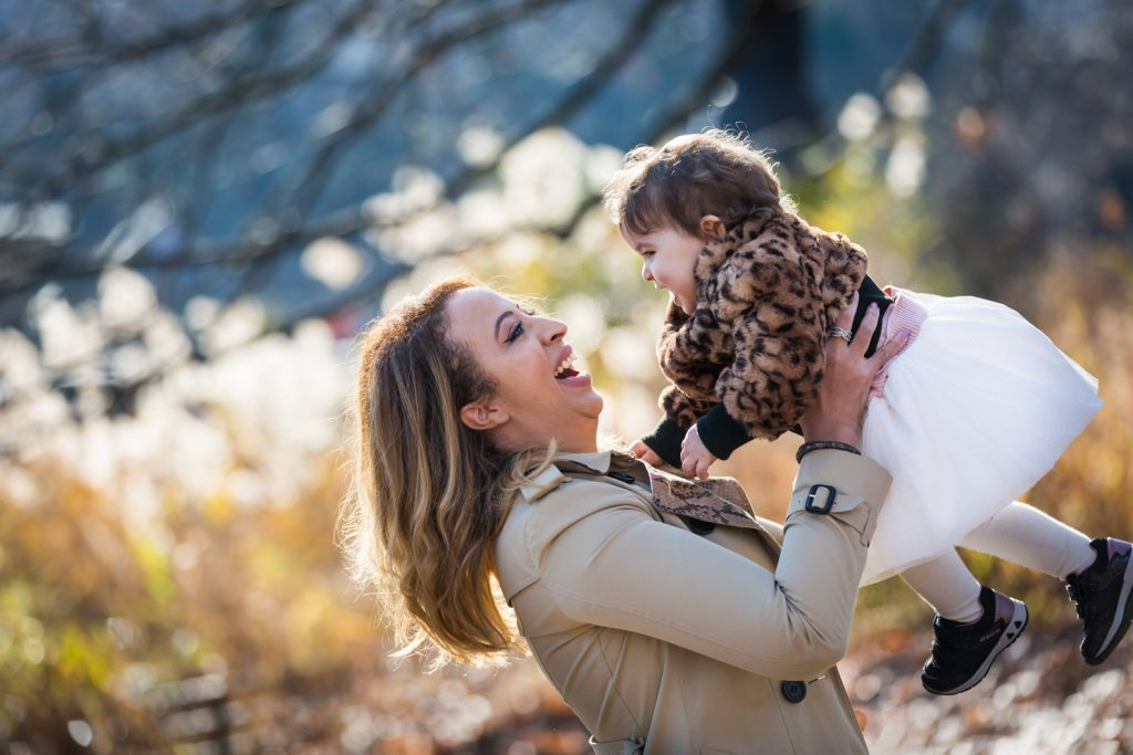 Mother lifting up little girl in Central Park