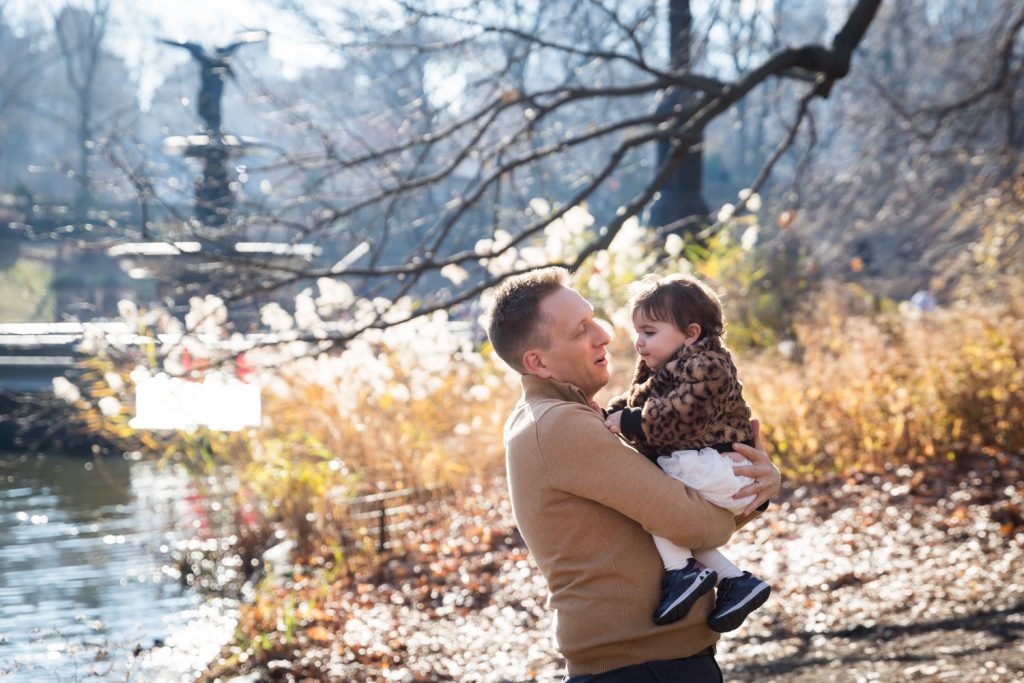 Father holding little girl with Bethesda Fountain in background for an article on Central Park holiday portrait tips