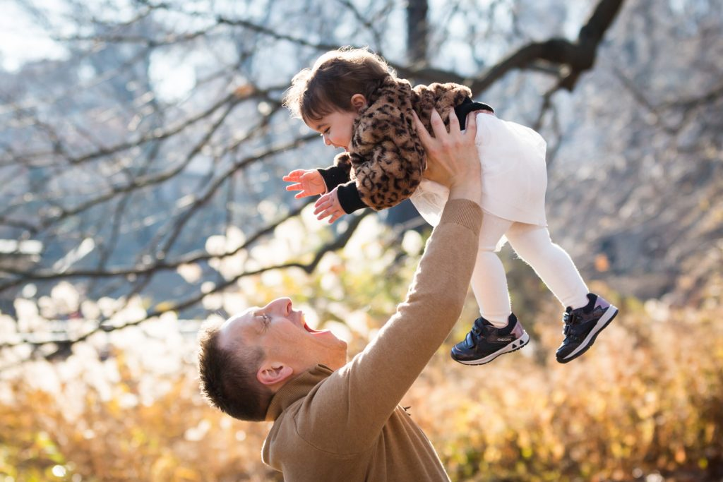 Father lifting up little girl in the air