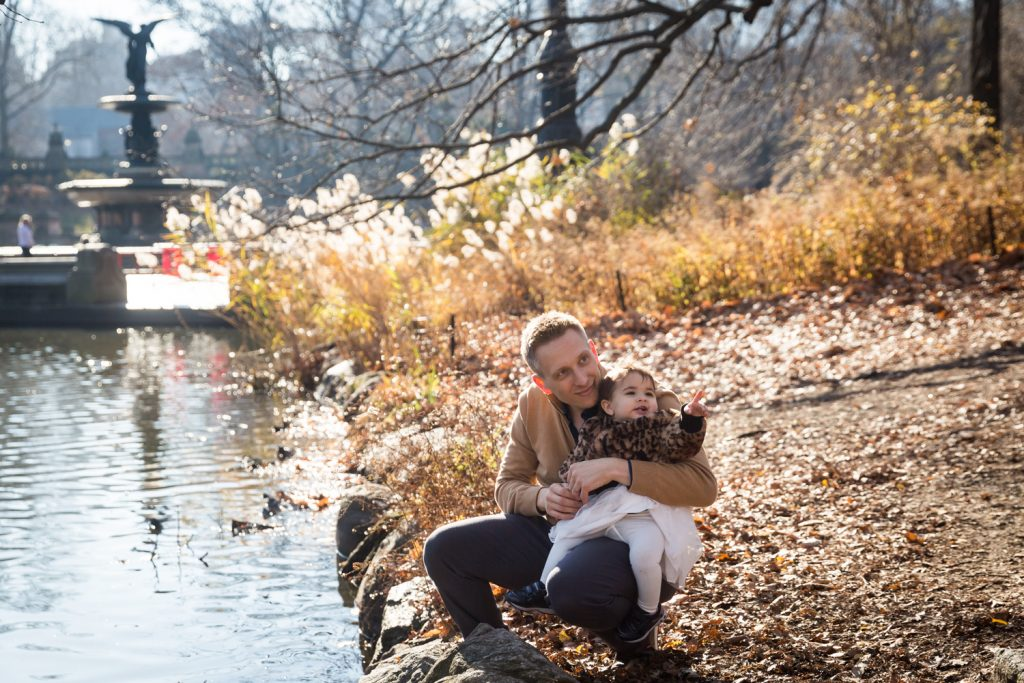 Father with little girl sitting beside Central Park Lake