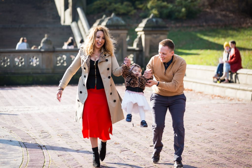 Parents swinging little girl at Bethesda Fountain for an article on Central Park holiday portrait tips
