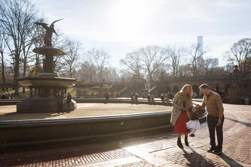Parents and little girl beside Bethesda Fountain