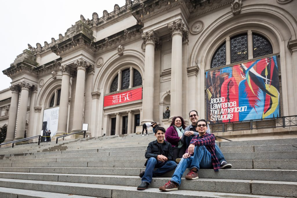 Family sitting on the steps of the Metropolitan Museum of Art in NYC