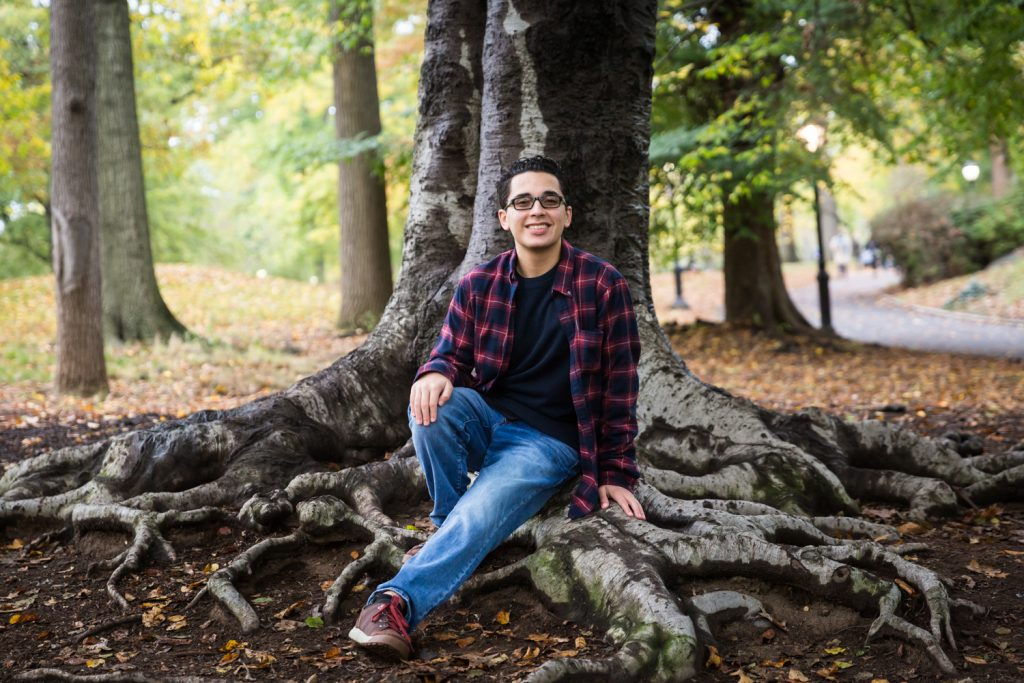 Young man sitting on tree roots during a Central Park senior portrait session