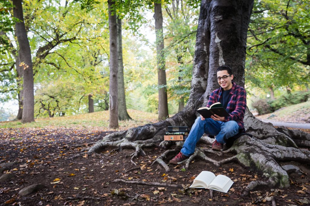 Young man under tree reading during a Central Park senior portrait session