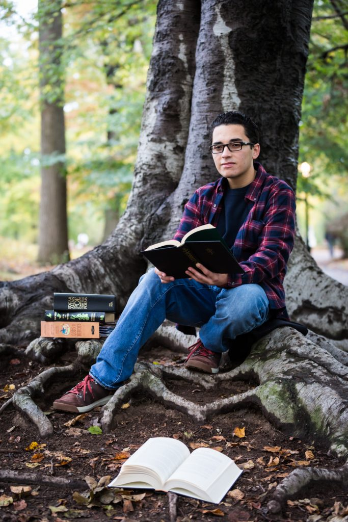 Young man holding book under tree during a Central Park senior portrait session