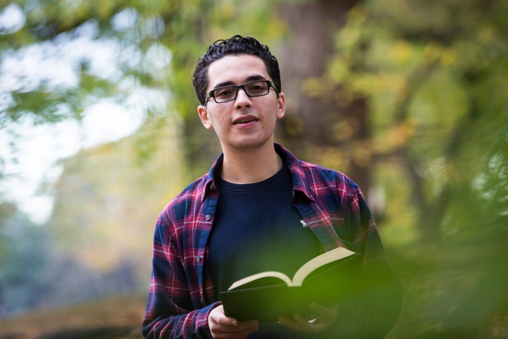 Young man holding book during a Central Park senior portrait session