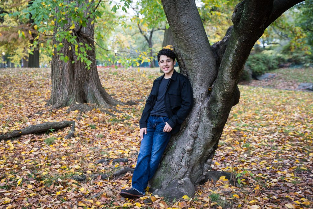 Young man leaning against tree in Central Park