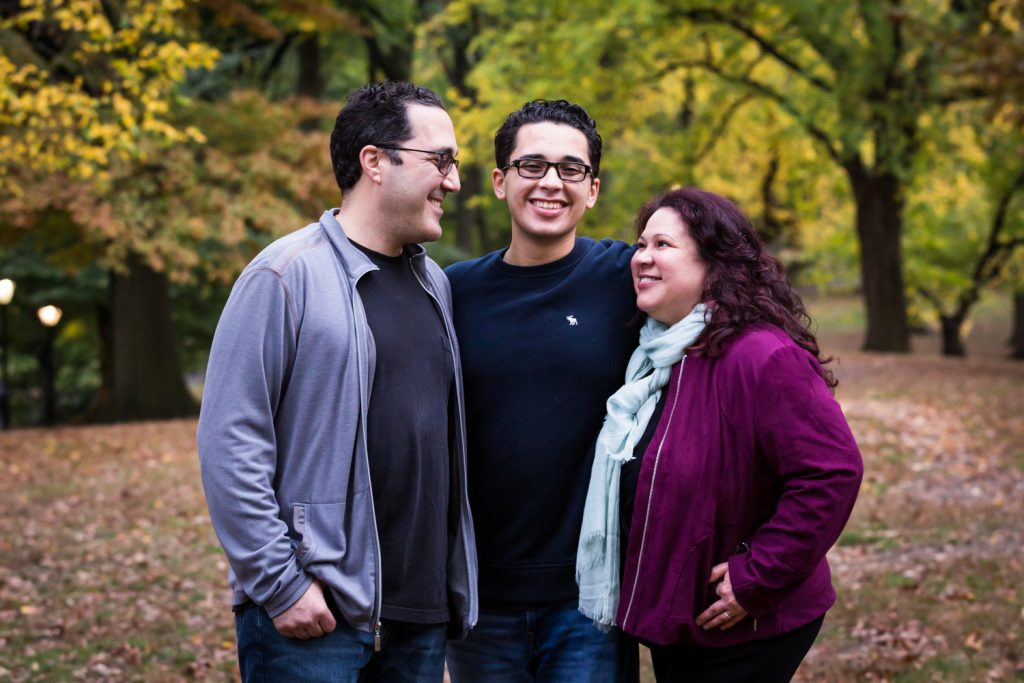 Parents surrounding son during a Central Park senior portrait session