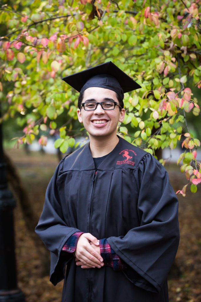 Young man wearing black cap and gown during a Central Park senior portrait session