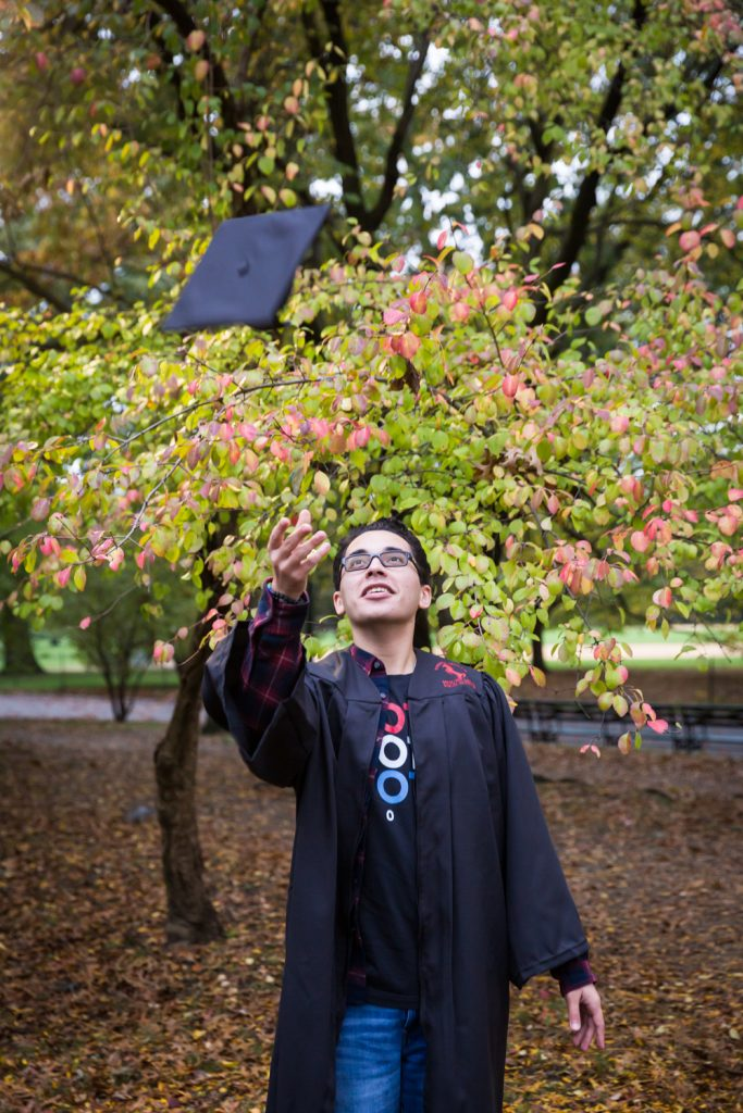 Young man tossing cap in air during a Central Park senior portrait session
