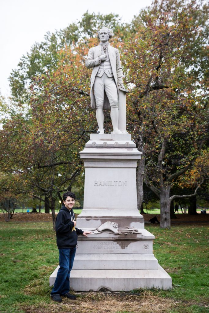Young man in front of Alexander Hamilton statue in Central Park