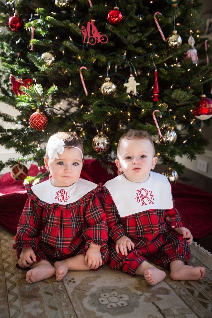 Two babies in matching plaid pajamas for an article on holiday family portrait ideas