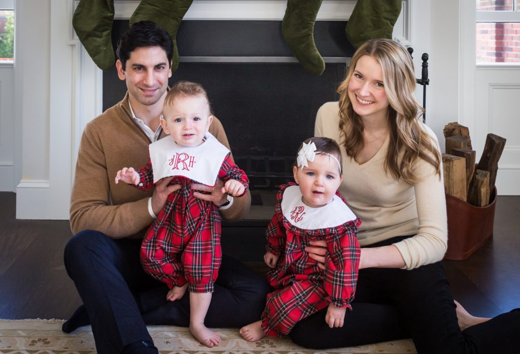 Parents holding baby twins in front of a fireplace for an article on holiday family portrait ideas