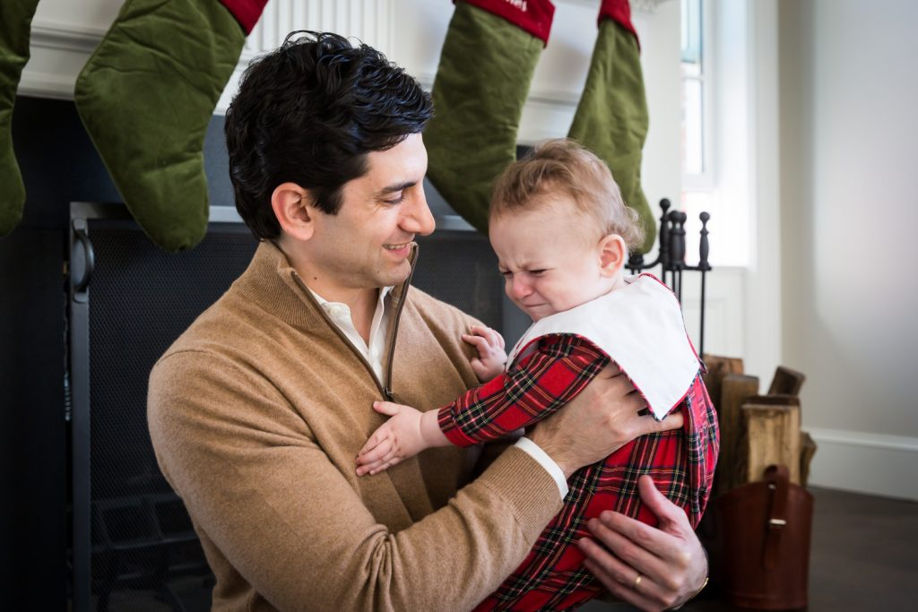 Father holding crying baby in front of fireplace