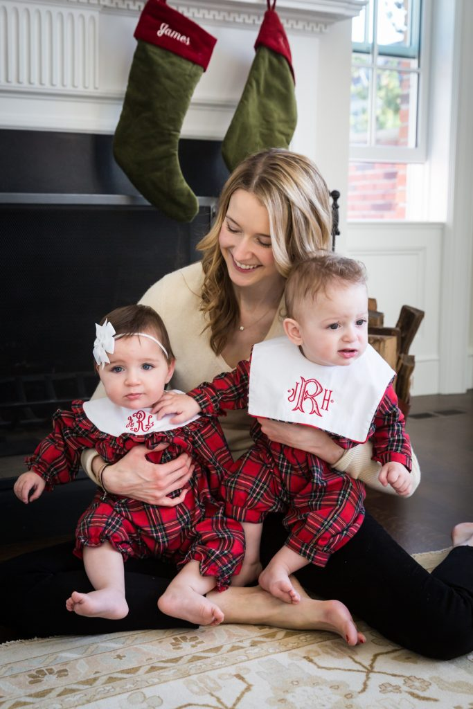 Mother holding baby twins wearing matching plaid pajamas