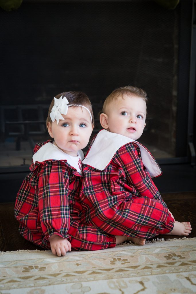Twin babies wearing matching plaid pajamas
