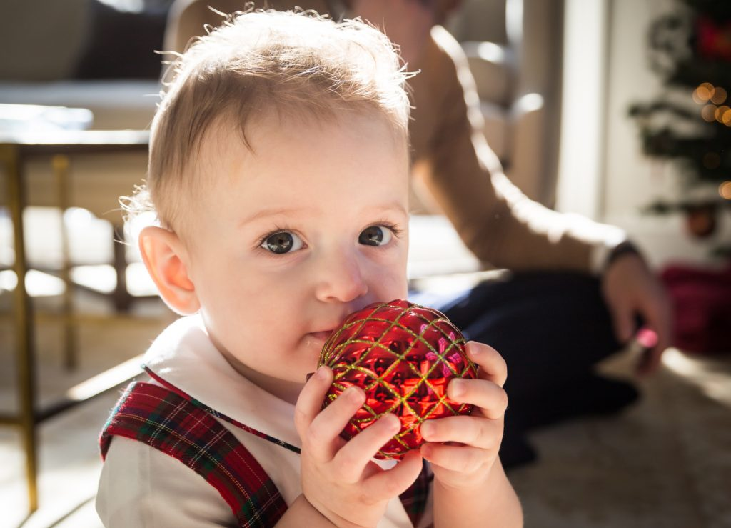 Baby boy holding Christmas ornament to his mouth