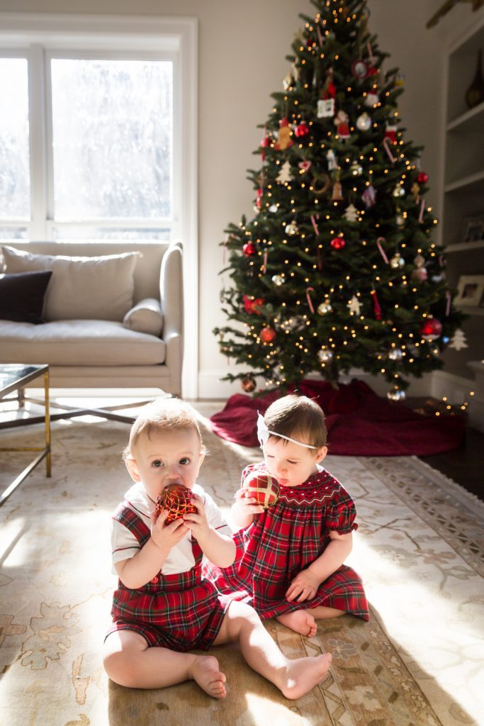 Two babies sitting on floor chewing on Christmas ornaments in front of tree