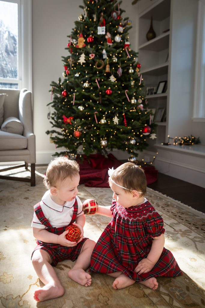 Two babies sitting on floor in front of Christmas tree