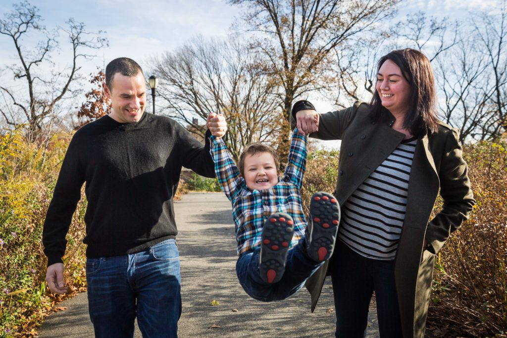 Parents swinging little boy by his arms for an article about a Forest Park photo shoot neighborhood discount offer