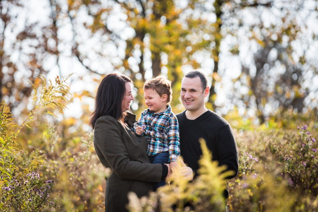Parents holding little boy in front of plants for an article about a Forest Park photo shoot neighborhood discount offer