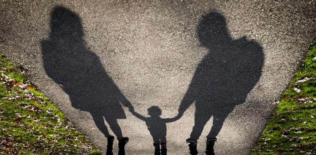 Shadow on ground of parents holding child by the hands