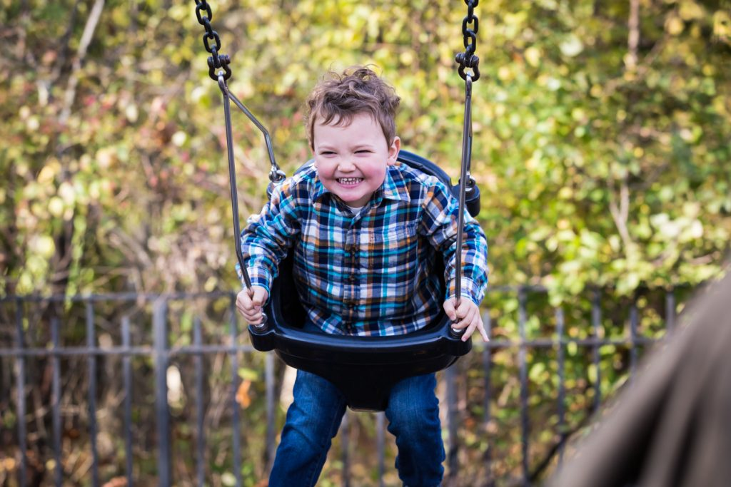 Little boy swinging in Forest Park playground