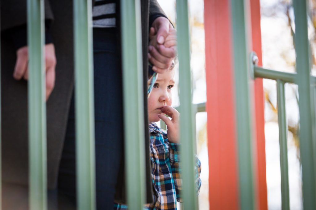Nervous little boy seen through playground railing