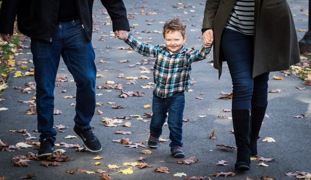 Little boy walking with parents hand-in-hand