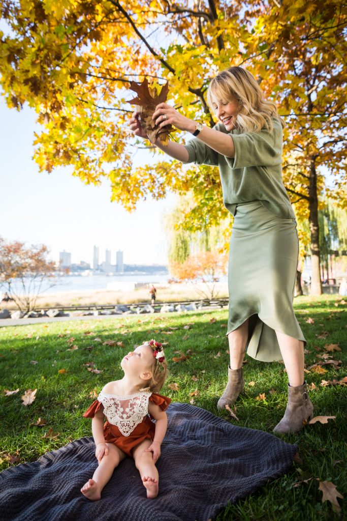 Mother dropping fall leaves down on little girl in Riverside Park
