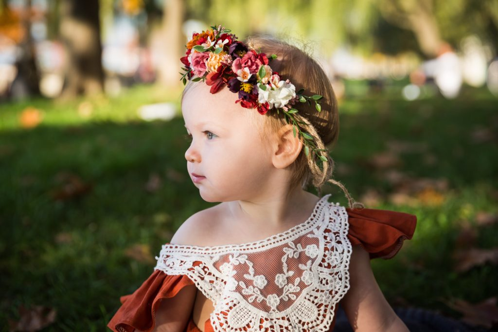 Profile photo of little girl wearing lace outfit and flowers in her hair