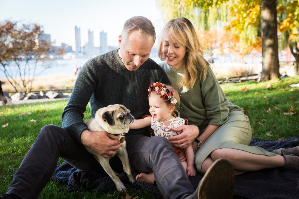Parents watching little girl pet dog for an article NYC golden hour portrait tips