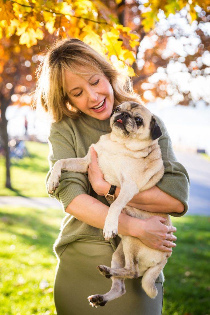 Woman holding pug dog in Riverside Park
