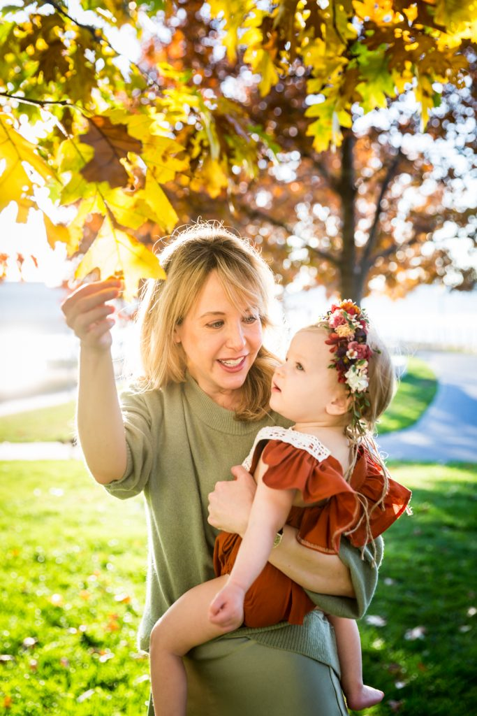 Mother showing leaf to baby girl for an article NYC golden hour portrait tips
