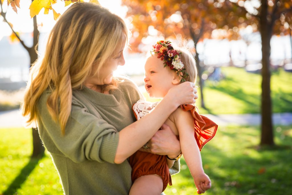 Mother holding baby girl for an article NYC golden hour portrait tips