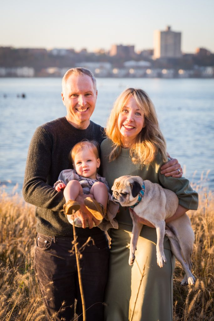 Parents holding little girl and dog in front of NYC waterfront