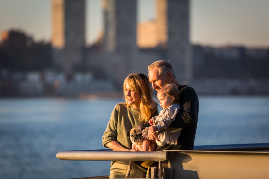Parents holding little girl and dog on pier for an article NYC golden hour portrait tips