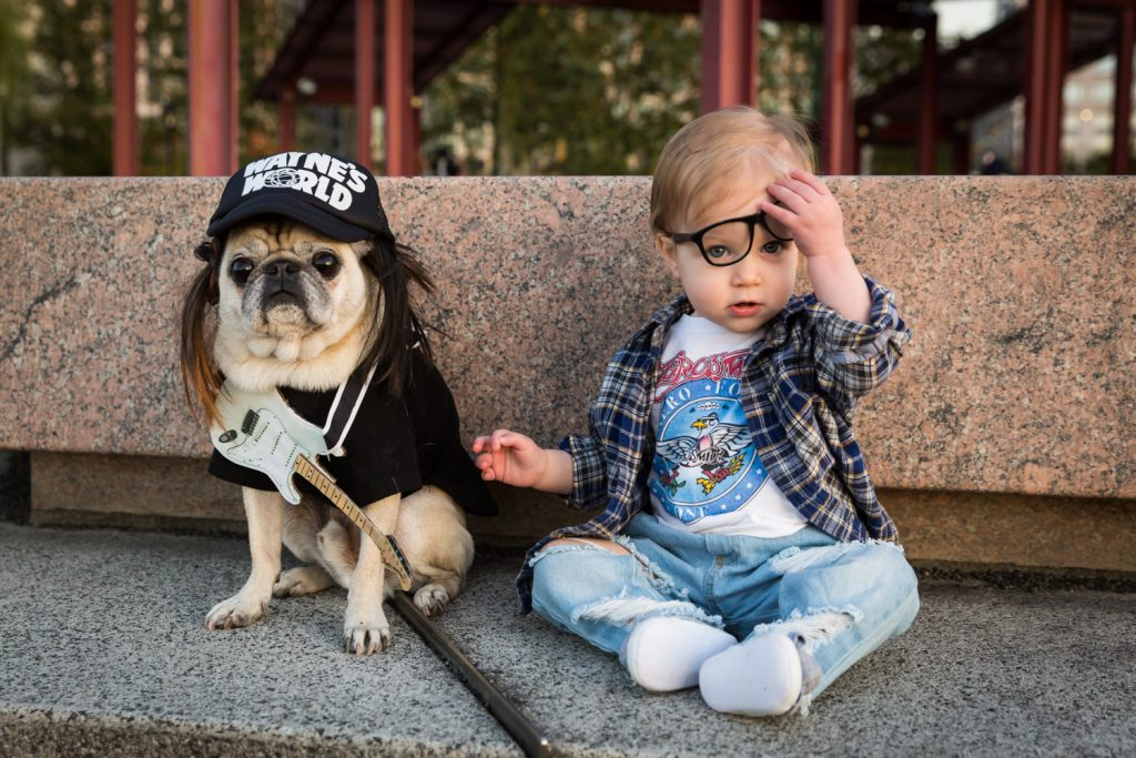 Little girl holding glasses with dog while dressed in Halloween costume