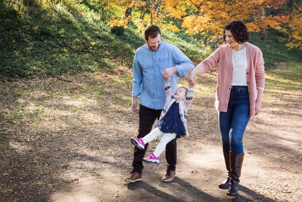 Parents swinging little girl in Riverside Park