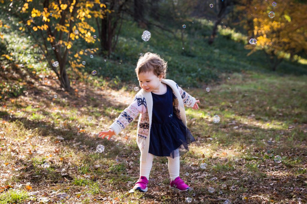 Little girl chasing bubbles in Riverside Park