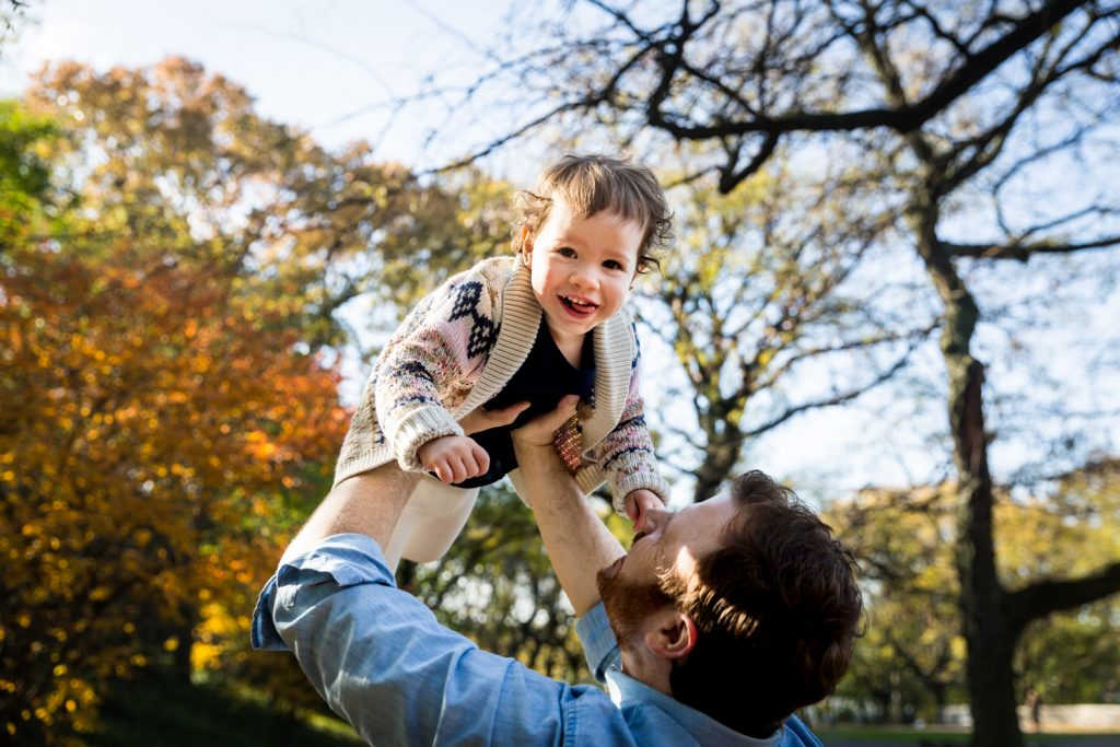 Riverside Park family photos of father holding little girl in the air