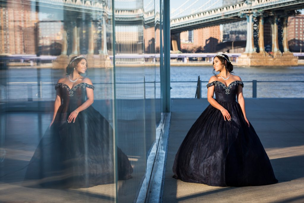 Reflection in window of girl wearing strapless ball ground Girl wearing tiara and coat with fur hood for an article on cold weather portrait tips