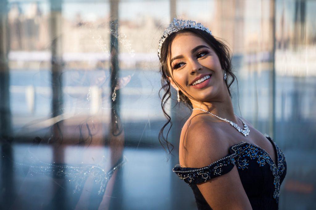 Girl wearing tiara looking back through window