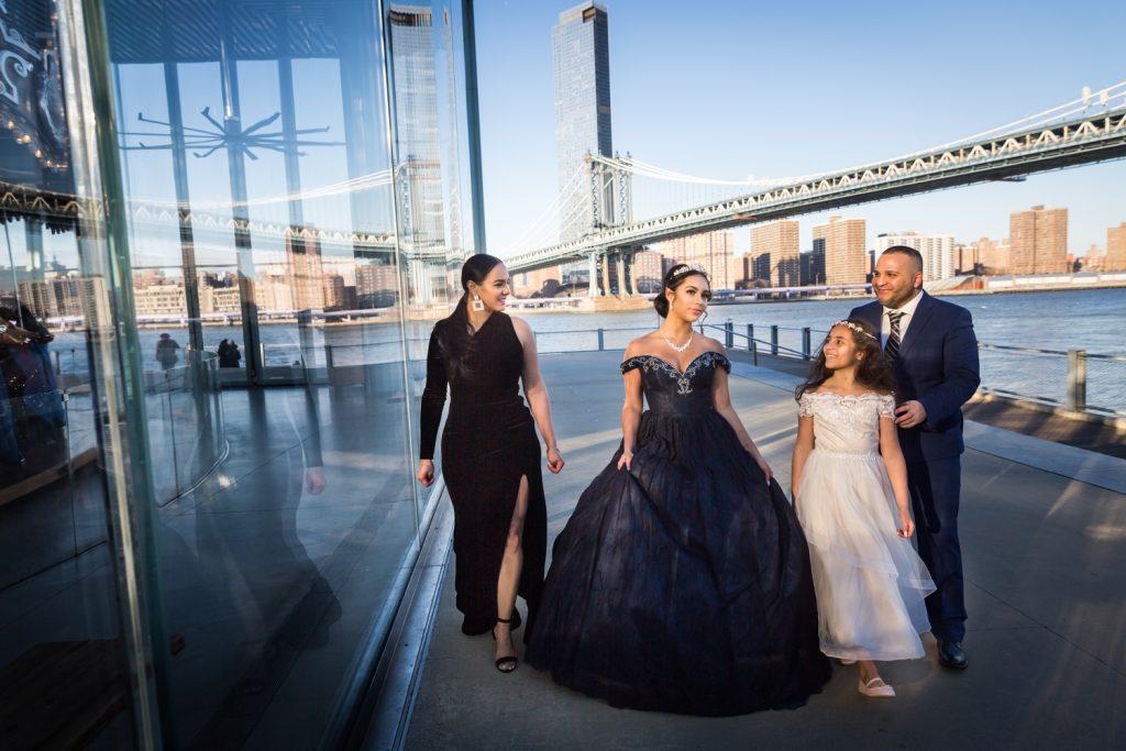 Family walking along side of Jane's Carousel in Brooklyn Bridge Park